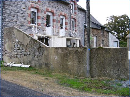 Concrete wall on stone house